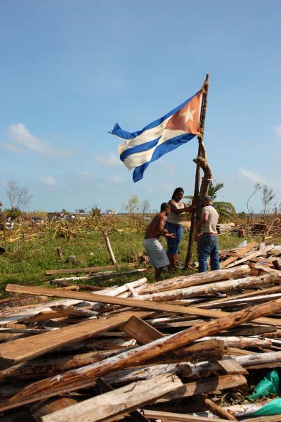 Pobladores izan una bandera cubana antes de comenzar reconstrucción de su vivienda en la Isla de la Juventud