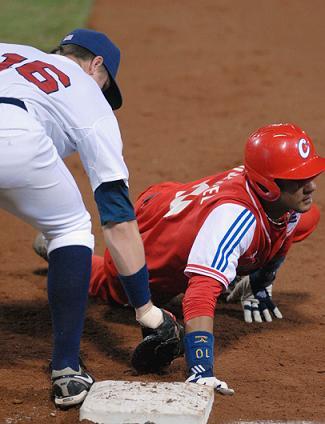 Jugada de Yulieshy Gourriel (rojo) en primera base